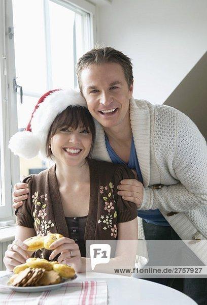 Mann und Frau mit Weihnachtshut und Lucia bun