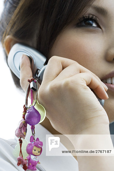 Woman using cell phone decorated with charms  close-up  cropped