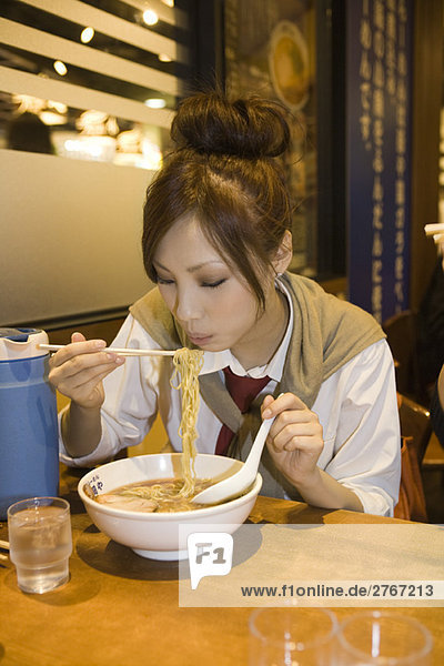 Young female eating bowl of ramen noodles in restaurant