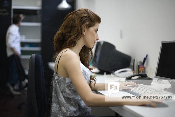 Frau arbeitet am Schreibtisch  Kollegin steht im Hintergrund
