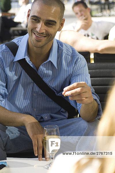 Mann bei einem Bier mit Freunden in einem Outdoor-Café