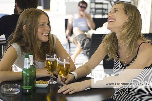 Zwei junge Freundinnen sitzen in einem Café im Freien und trinken ein Glas Bier.