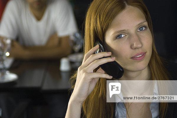 Frau hält Handy ans Ohr  lächelt in die Kamera