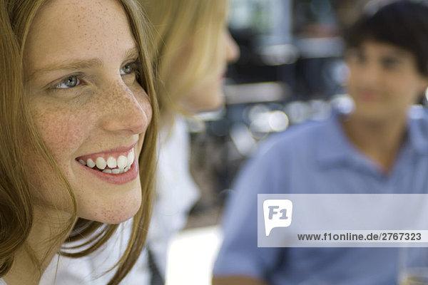 Junge Frau lächelt  Freunde im Hintergrund