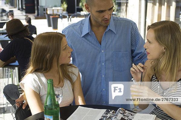 Mann im Gespräch mit zwei jungen Frauen im Outdoor-Café