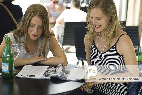 Zwei junge Freundinnen sitzen im Outdoor-Café und schauen sich zusammen das Magazin an.