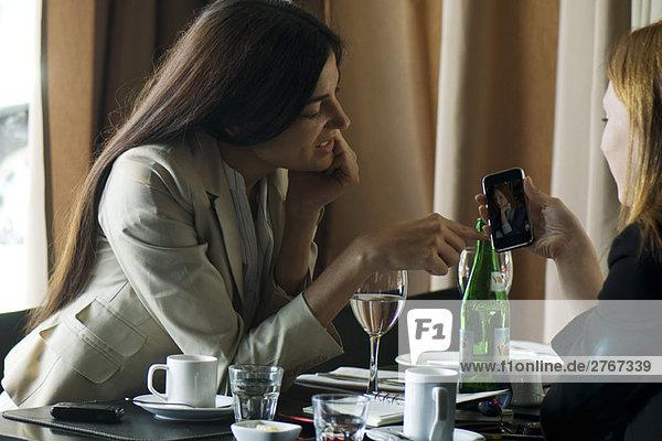Zwei Frauen sitzen im Cafe und schauen zusammen auf das Fotophon.