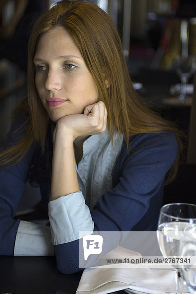 Gelangweilte Frau sitzt im Cafe