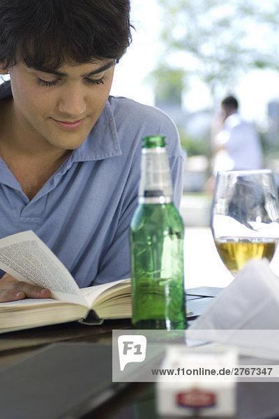 Junger Mann liest Buch und trinkt ein Bier in einem Café im Freien.