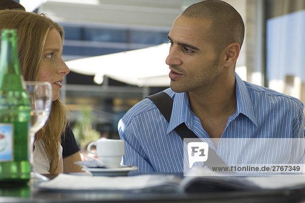 Mann und Frau sitzen in einem Café im Freien und unterhalten sich ernsthaft.