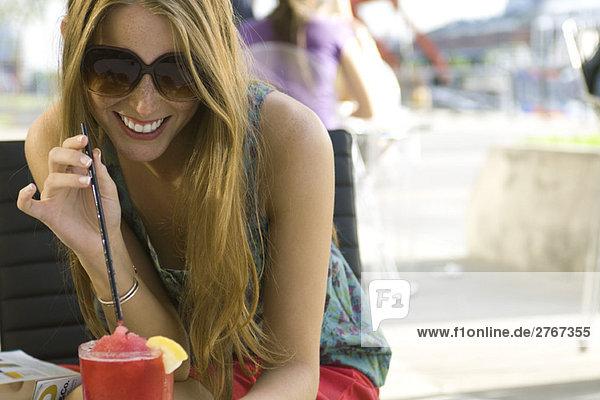 Junge Frau trinkt kühles Getränk im Freien