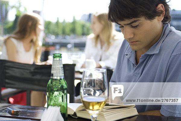 Junger Mann sitzt im Café  liest Bücher und trinkt ein Bier.