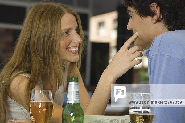 Junges Paar im Café  Frau berührt die Wange des Mannes