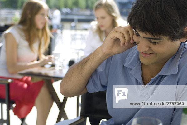 Junger Mann mit Handy im Freien
