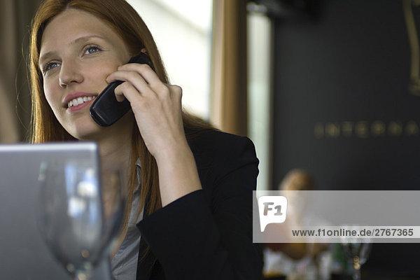 Frau mit Handy im Restaurant