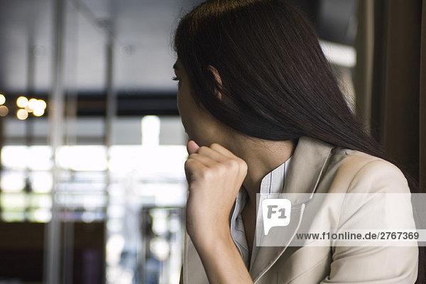 Junge Frau in einem Restaurant  die über die Schulter zur Tür schaut