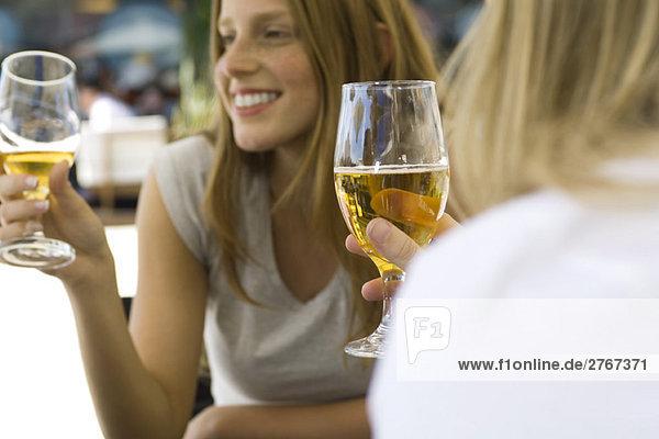 Junge Frauen trinken Bier im Straßencafé  gepflanzt