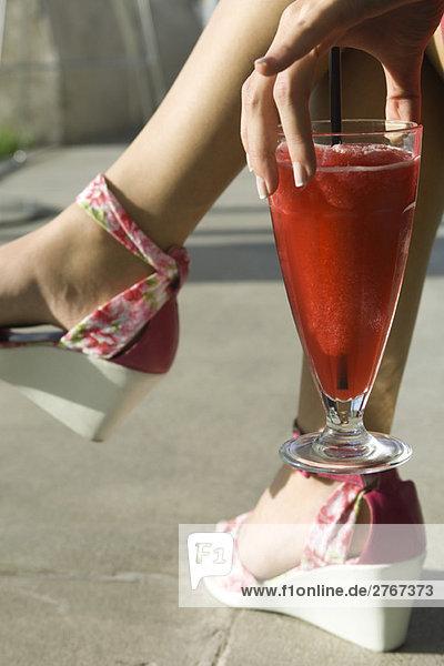 Frau hält Daiquiri zu Fuß  Ausschnittansicht