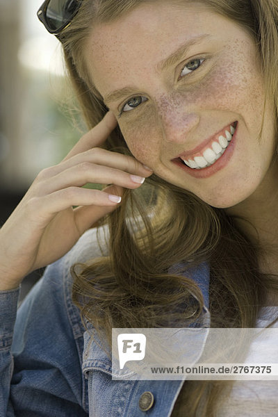 Junge Frau mit Sommersprossen lächelnd vor der Kamera  Portrait