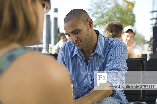 Leute  die auf dem Bürgersteig sitzen  konzentrieren sich auf den Menschen im Mittelgrund.