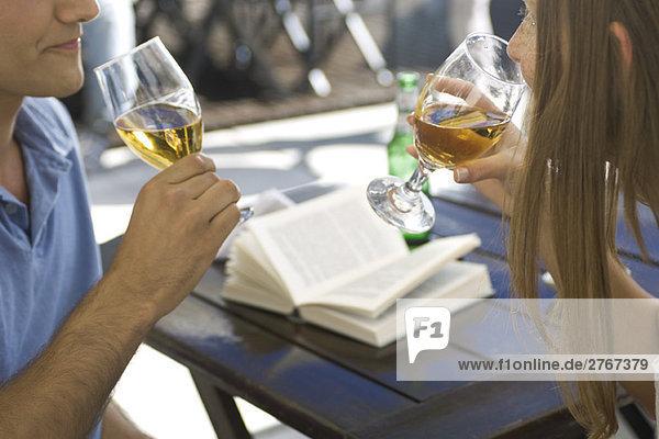 Paar Bier trinken im Freien  offenes Buch auf dem Tisch im Hintergrund