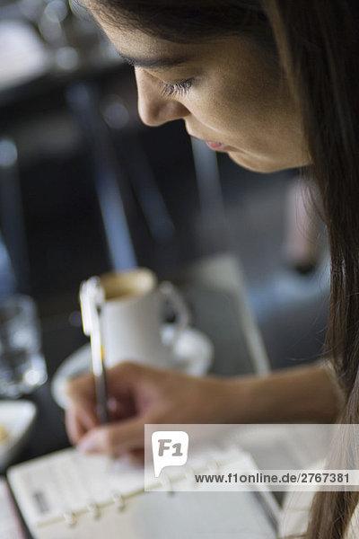 Frau beim Schreiben in der Agenda  abgeschnitten