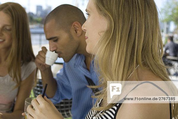 Junge Frau sitzend mit Freunden im Straßencafé  Nahaufnahme