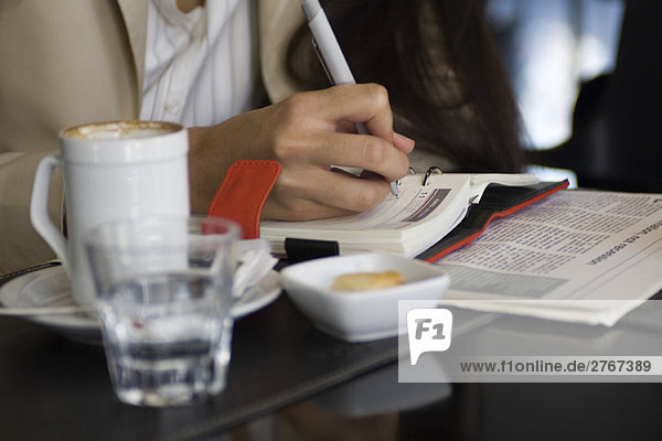 Frau sitzt im Cafe  schreibt in der Agenda  Ausschnittansicht