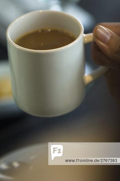 Kaffeetasse mit der Hand aufheben