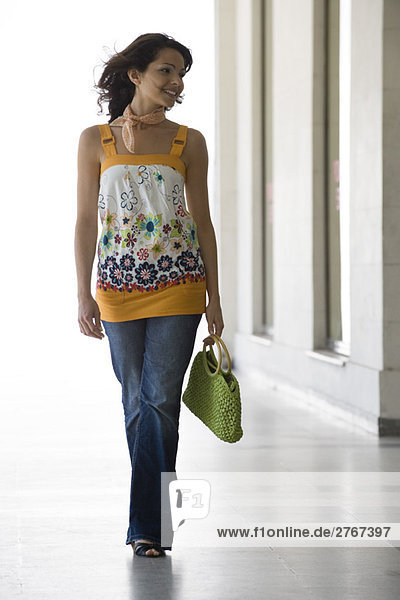 Modische junge Frau beim Gehen  volle Länge