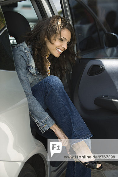 Junge Frau steigt aus dem Auto  zieht sich einen Schuh an