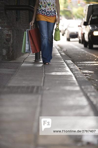 Frau geht auf dem Bürgersteig  trägt Einkaufstaschen  Blickwinkel niedrig