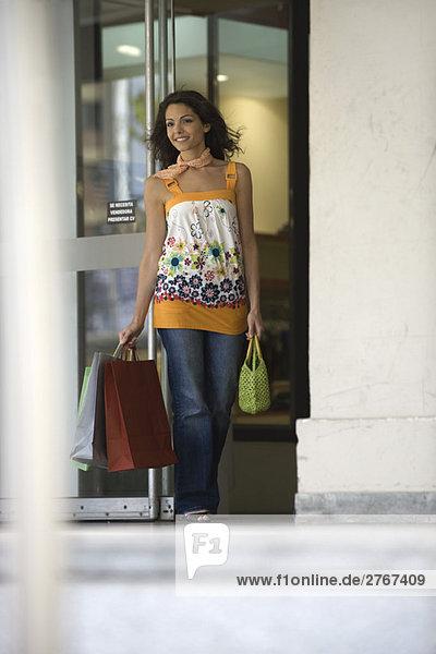 Junge Frau verlässt den Laden mit Einkaufstaschen  lächelnd