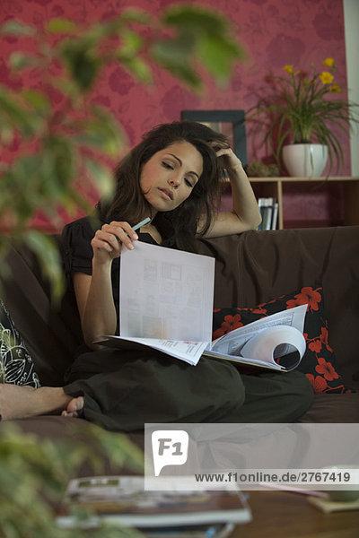 Junge Frau auf dem Sofa sitzend  Dokumente lesend