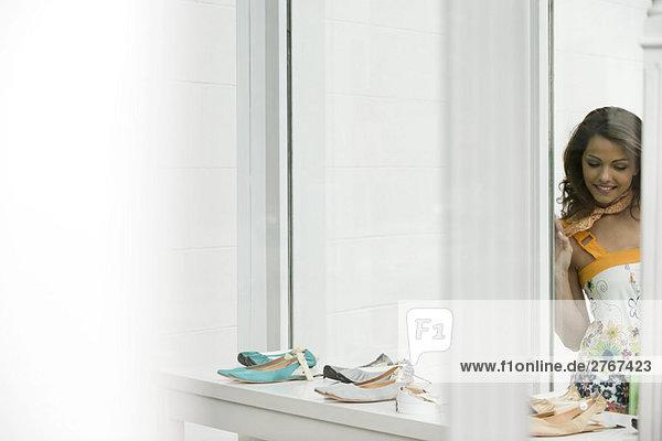 Junge Frau betrachtet Schuhe im Schaufenster