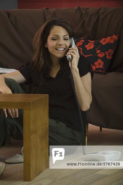 Frau sitzt auf dem Wohnzimmerboden  spricht auf dem Festnetztelefon