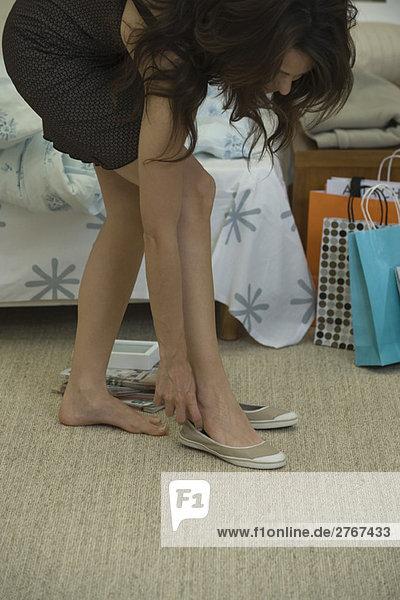 Junge Frau beugt sich vor  um Freizeitschuhe anzuziehen.