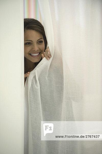 Frau guckt aus dem Vorhang  lächelnd