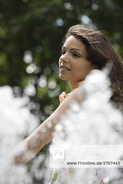 Junge Frau lächelt im Freien  Fontänenspray im Vordergrund