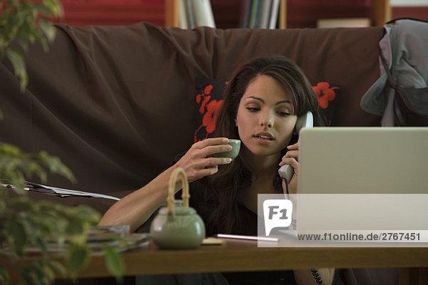 Junge Frau sitzt am Kaffeetisch mit Telefon und Laptop und hält eine Tasse Tee.