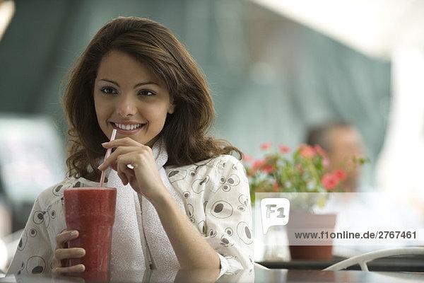 Junge Frau trinkt Smoothie im Straßencafé