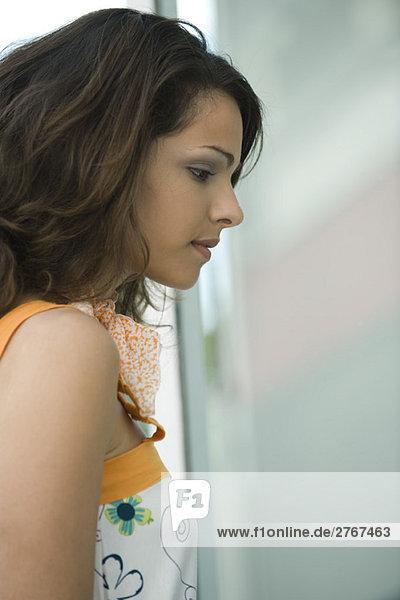 Junge Frau schaut ins Fenster  Profil