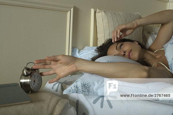 Junge Frau im Bett liegend  stiller Wecker
