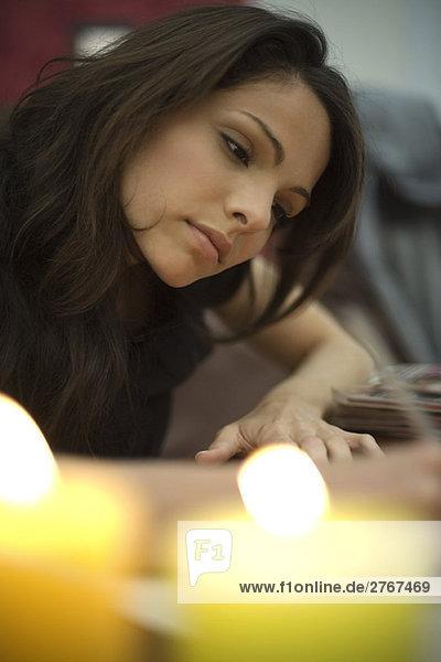 Frau beim Schreiben  Kerzen brennen im Vordergrund