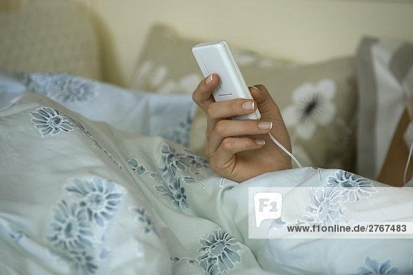 Frau im Bett  hält MP3-Player  abgeschnittene Ansicht der Hand