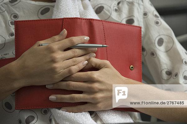 Frau hält Tagebuch auf der Brust  Ausschnittansicht