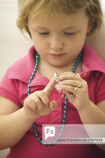 Kleines Mädchen spielt mit Modeschmuck  zieht einen Ring an