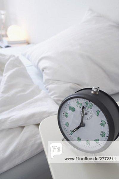 Stillleben mit Wecker auf Sideboard mit leeren Bett im Hintergrund