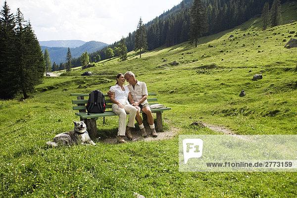 Ganzkörper-Portrait von reifes Paar mit Hund auf Bank in den Bergen sitzen