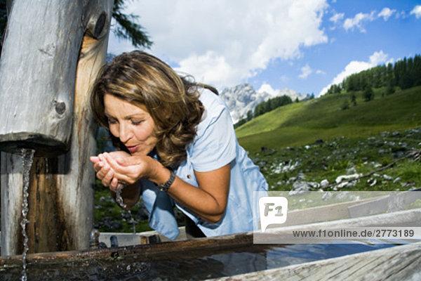 Porträt von Frau trinkt aus Brunnen in den Bergen